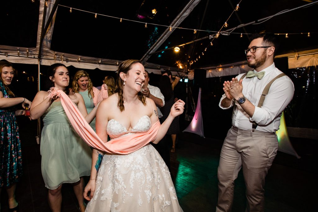 A bride is lassoed by a pink scarf as the groom watches