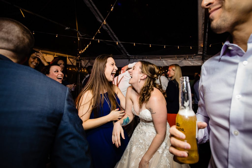 Bride laughs hysterically with friend on wedding dance floor