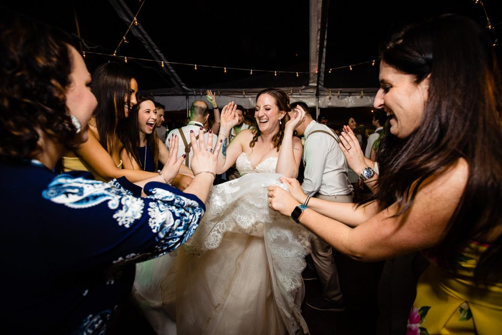 Friends use the brides dress to fan her during her tented wedding reception at Stamford Museum and Nature Center