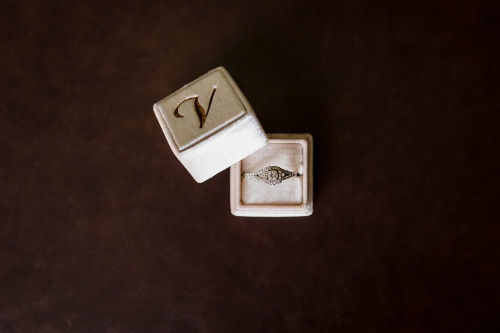 Wedding rings in a box with the letter V.
