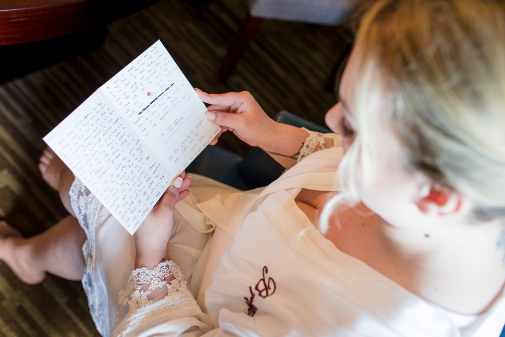 A bride reads her letter from the groom at central MA wedding.