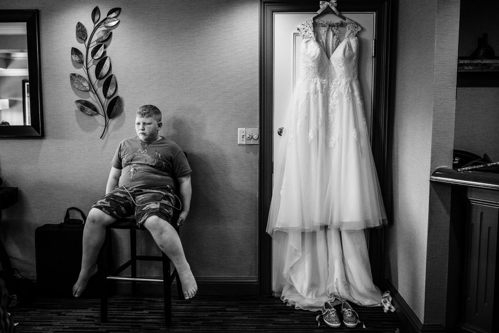 A young boy sits next to a wedding gown during wedding prep in central MA.