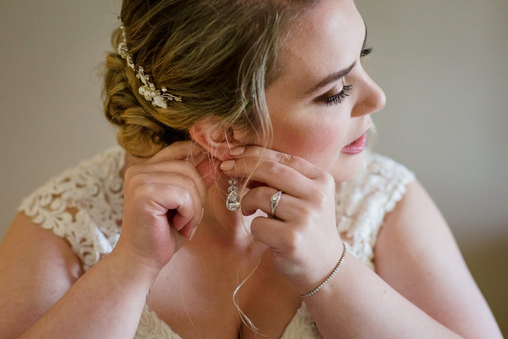 A bride puts in her earrings for her central MA wedding.