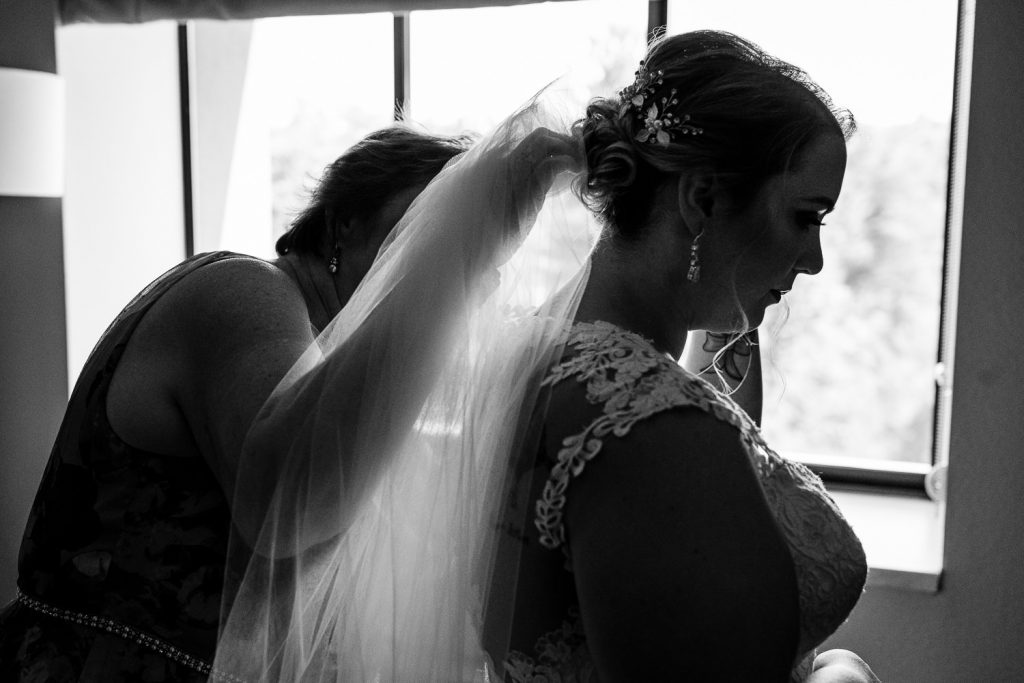 Mom helps daughter with wedding veil in Leominster, MA wedding.