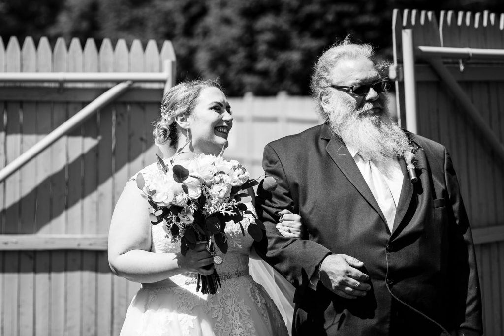 A bride and her dad walk down the outdoor aisle at the 228 in Sterling.