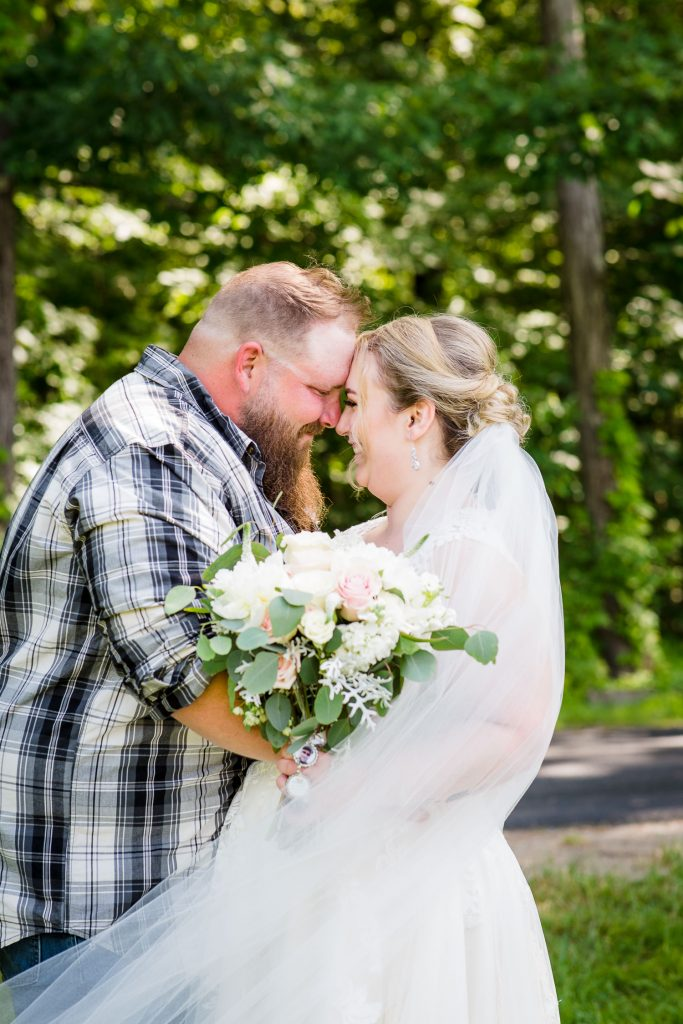 A bride and groom touch foreheads during wedding portraits at 228 in Sterling.