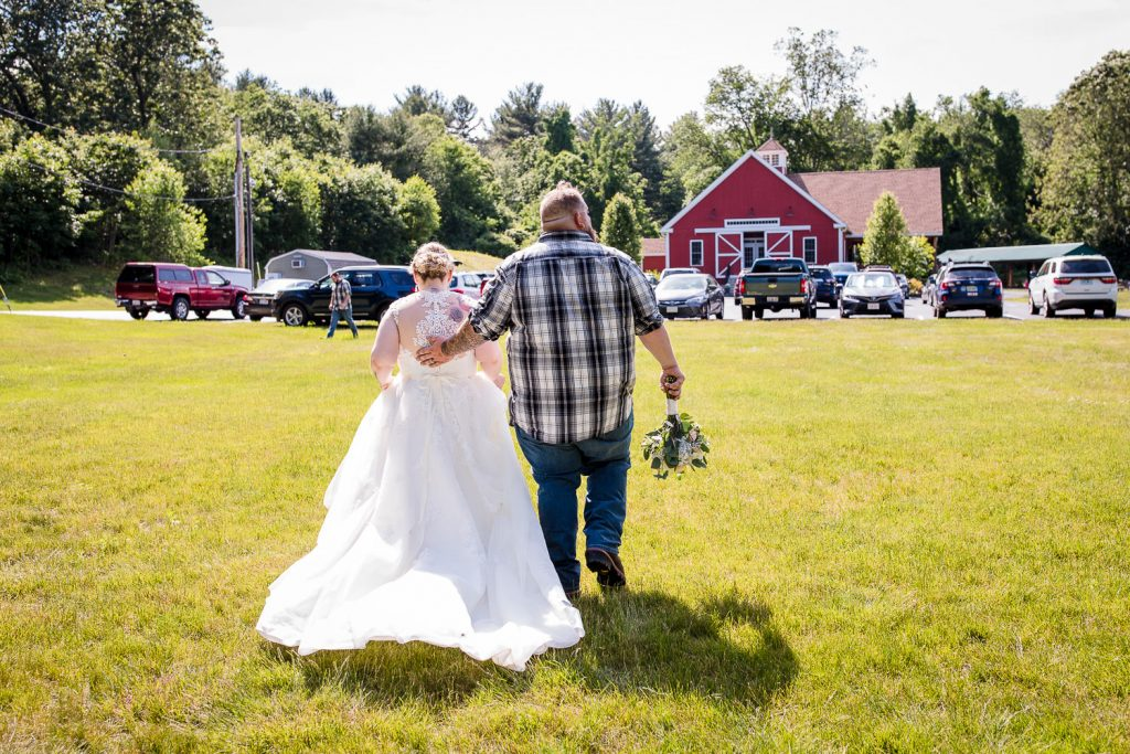 A bride and groom walk towards their barn wedding venue in central MA.