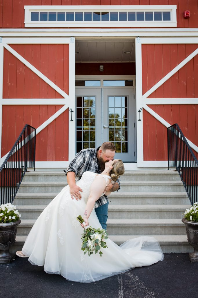 The groom dips his bride in front of the 228 Sterling red barn in central MA.