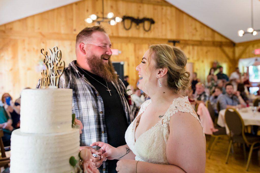A bride and groom laugh and eat cake at 228 Sterling central MA barn wedding