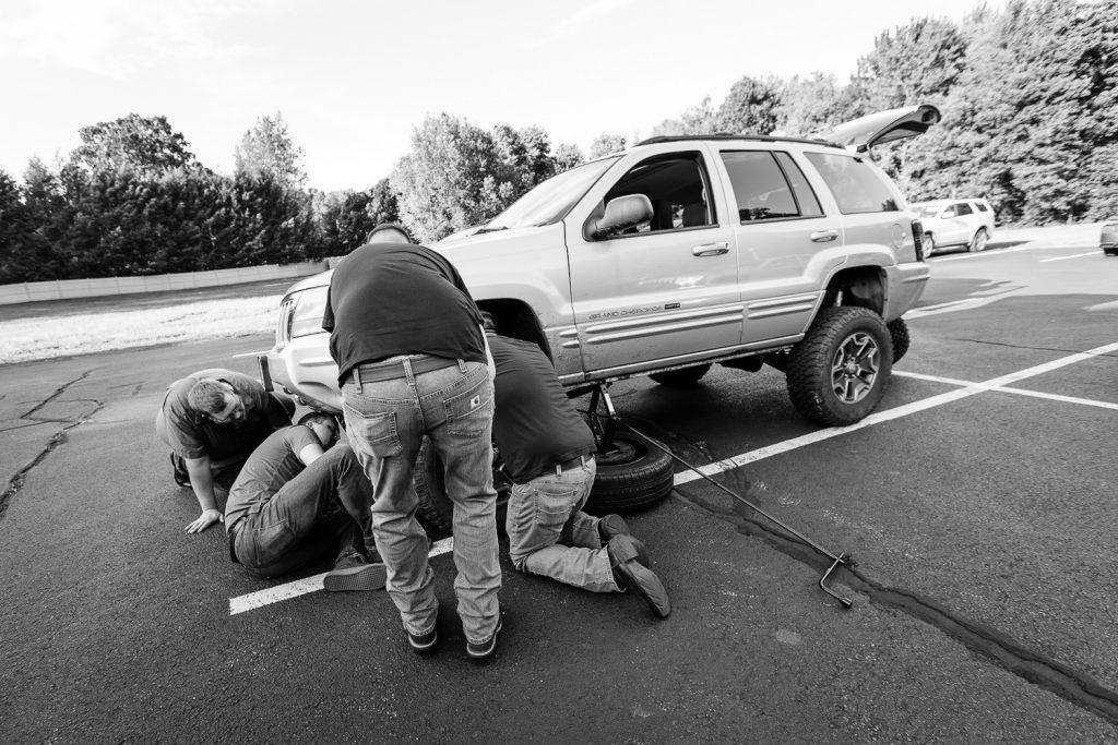 Guys fix a car at central MA barn wedding