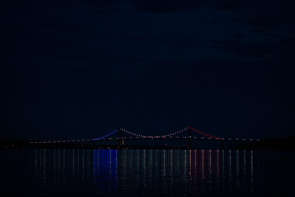 Mt. Hope Bridge in Bristol, RI lit up red white and blue for fourth of july.