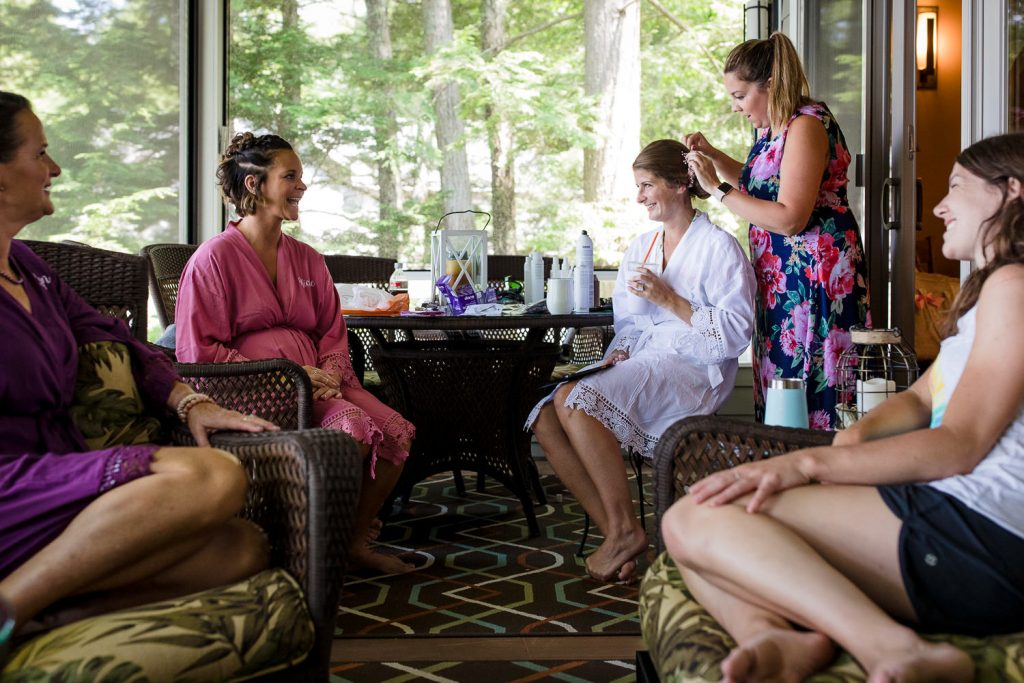 A bride and friends laugh while getting ready for a wedding on Merrymeeting Lake NH