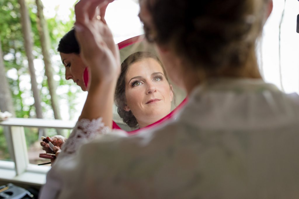A bride looks at herself in the mirror before her Merrymeeting Lakes Region NH wedding