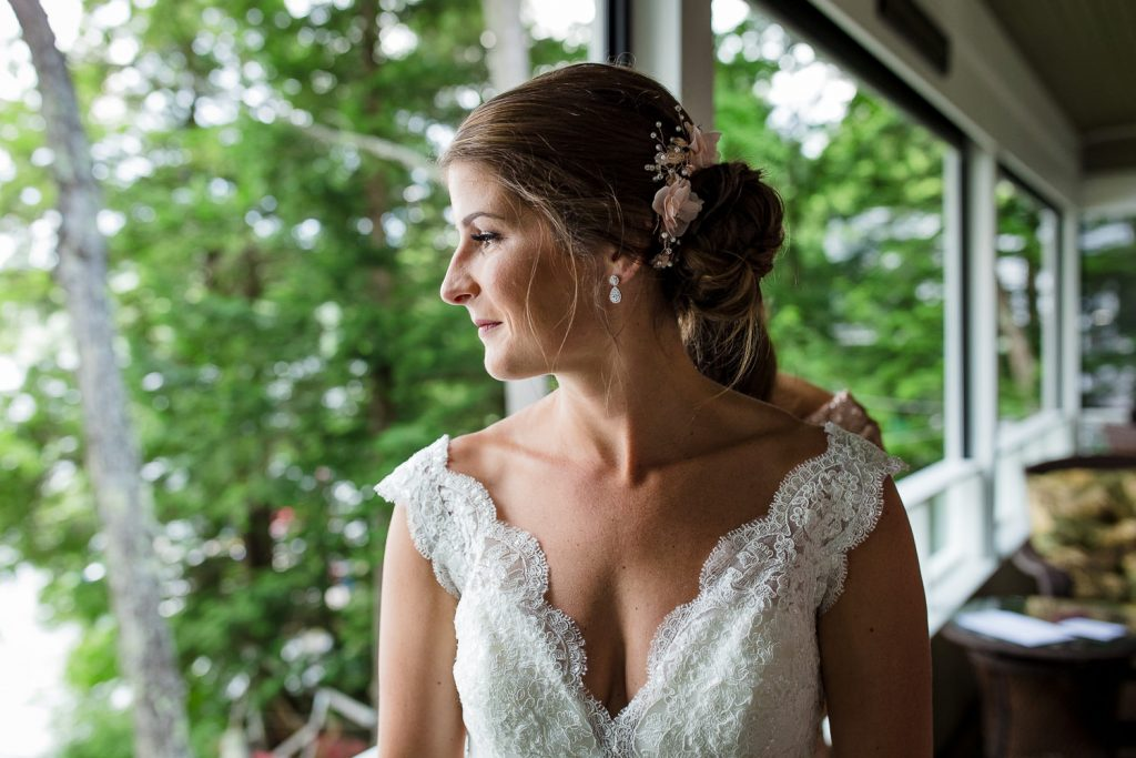 The bride looks out over Merrymeeting Lake before her NH lakes region wedding