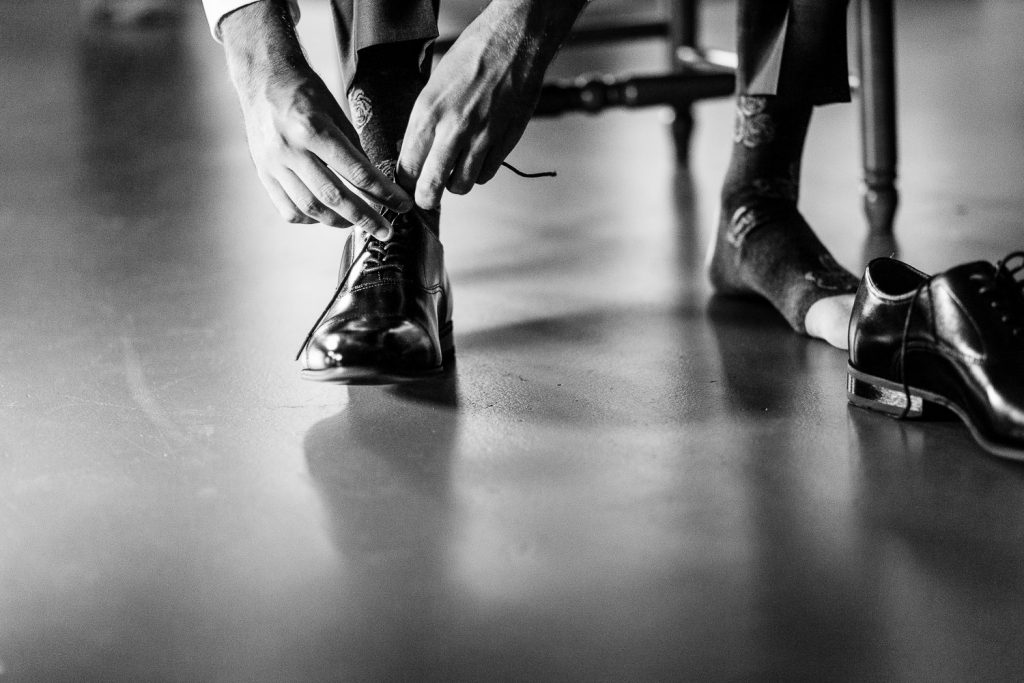 The groom puts on his socks and shoes before his Merrymeeting Lake NH wedding