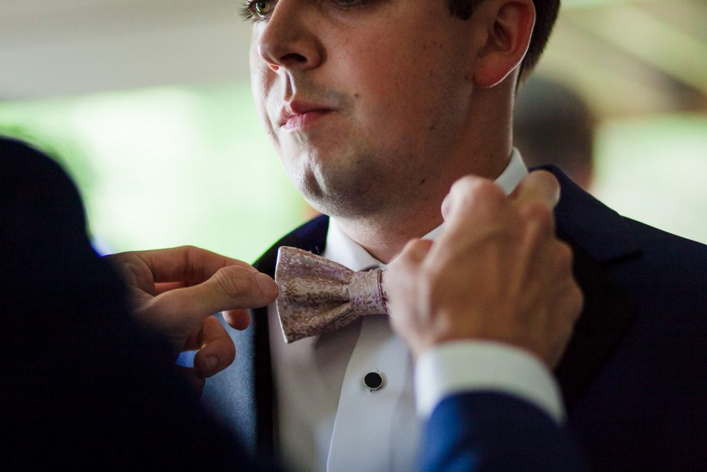 The groom gets help with his bowtie prior to his wedding on Merrymeeting Lake NH
