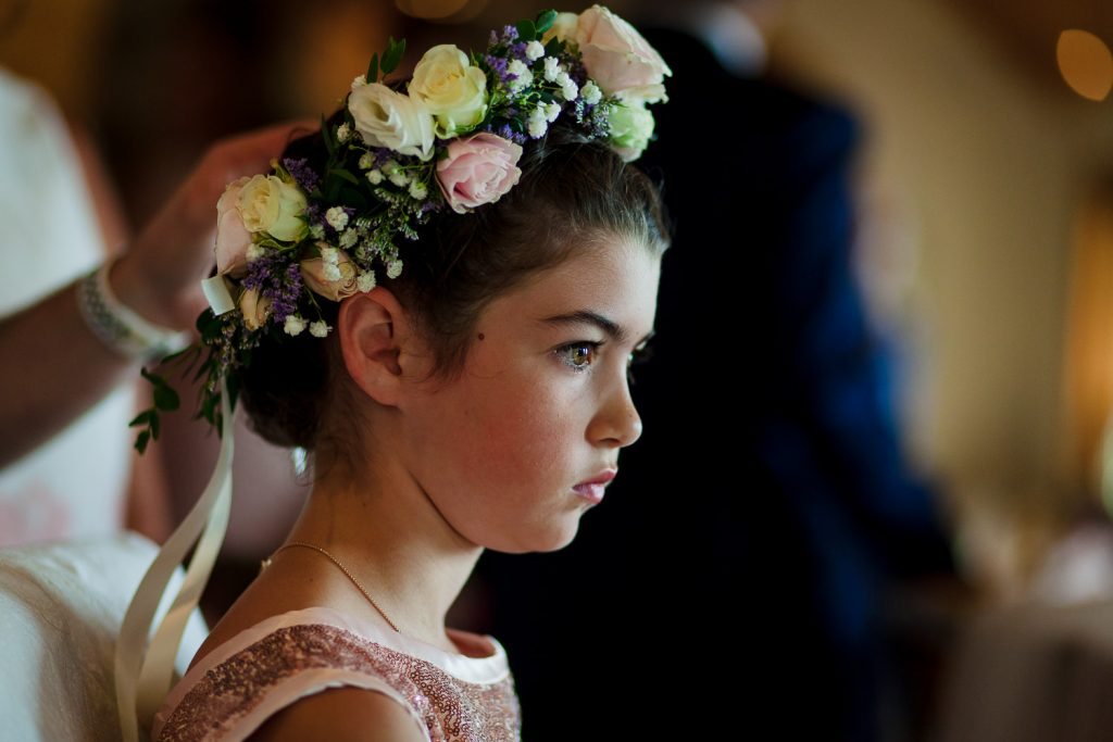 A flower girl gets a flower crown at a Lake Region NH Wedding