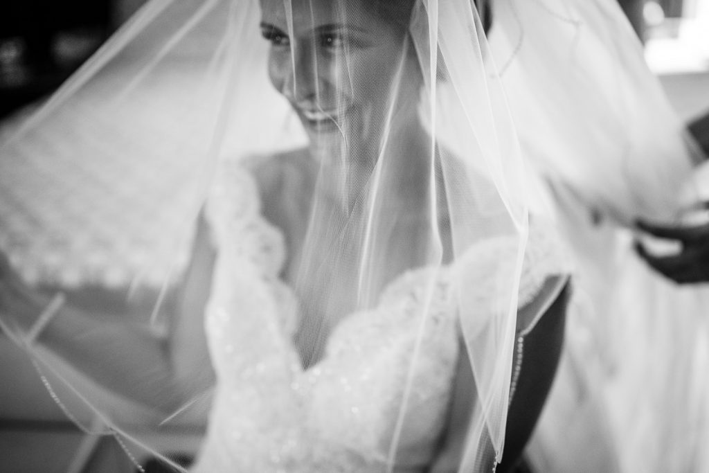 The bride laughs as she puts on her veil at her Merrymeeting Lake NH wedding
