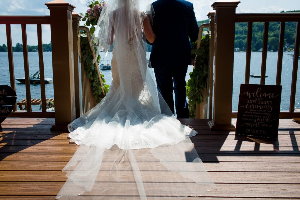 The bride and her father walk down a cinderella staircase at Merrymeeting Lake NH wedding