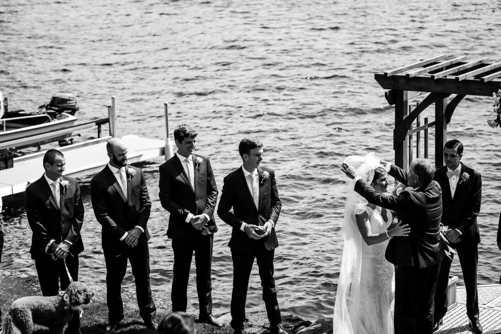 The father of the bride gives his daughter away at a dockside Merrymeeting Lake NH Wedding