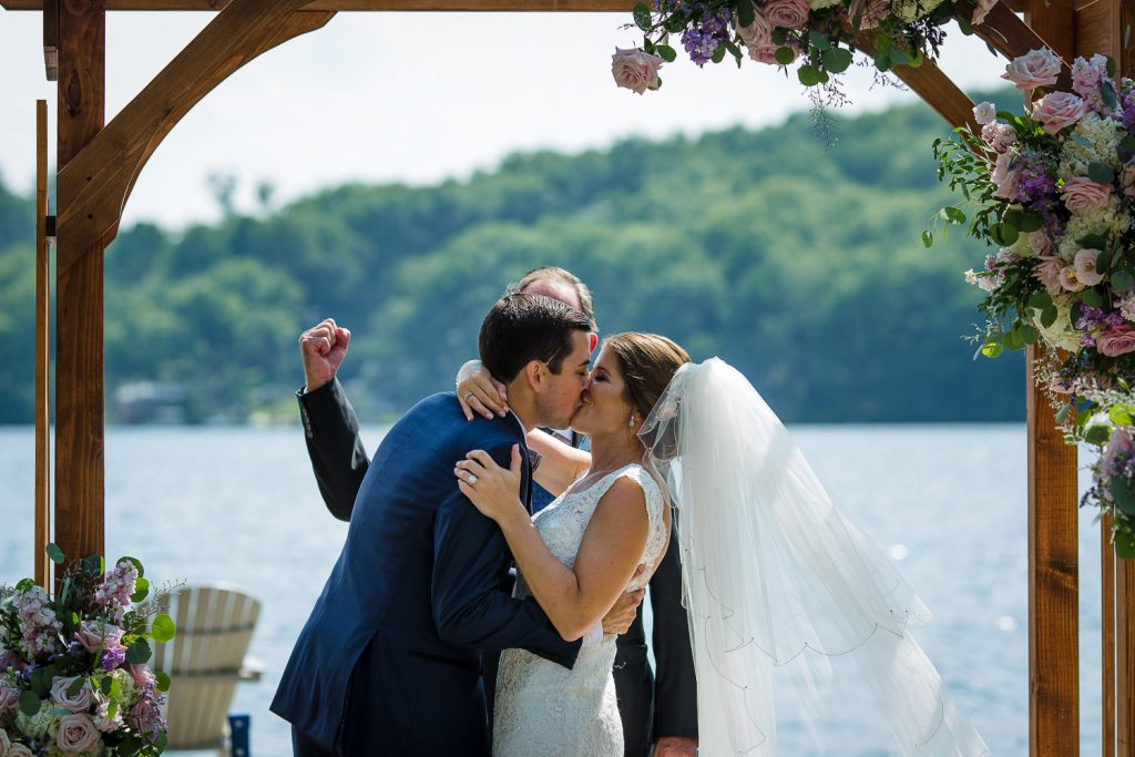 The officiant fist pumps behind the bride and groom kissing at their Merrymeeting Lake NH wedding ceremony.