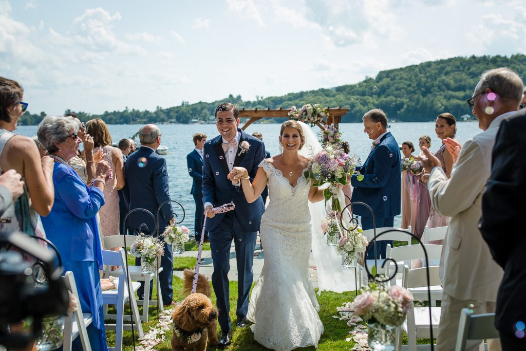 The bride and groom and their dog recess down the aisle at their Merrymeeting Lake wedding ceremony