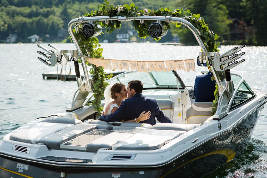 The bride and groom kiss in their getaway boat with just married sign on Merrymeeting Lake