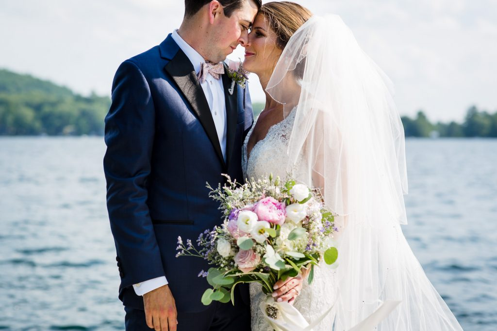 The bride and groom touch foreheads during wedding portraits on Merrymeeting Lake NH wedding