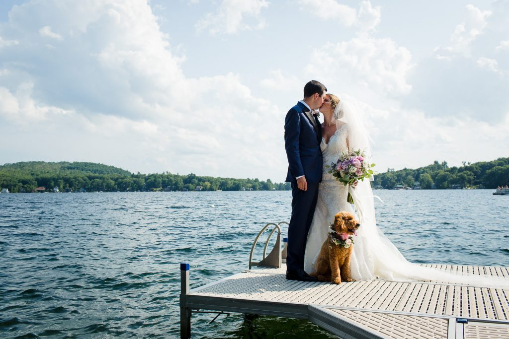 The bride groom and their dog stand on a dock at their Merrymeeting Lakes Region NH wedding