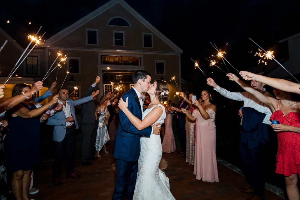 The bride and groom kiss during their sparkler exit at their wedding at the Barn at Pickering House in Wolfeboro, NH.