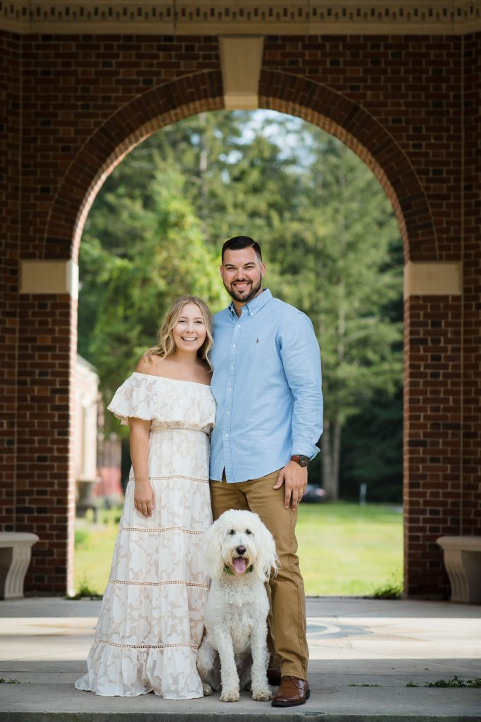 Couple posing for engagement photos at Hall of Springs in Saratoga Springs, NY with their dog