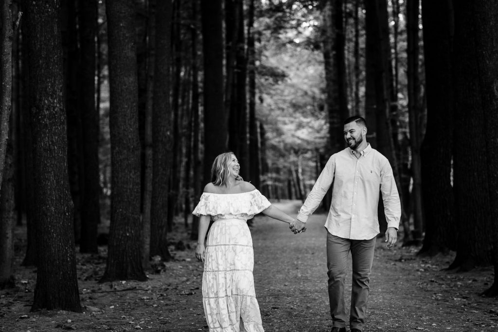 Couple posing along a hiking trail in Saratoga Spa State Park in Saratoga Springs, NY for their engagement photos