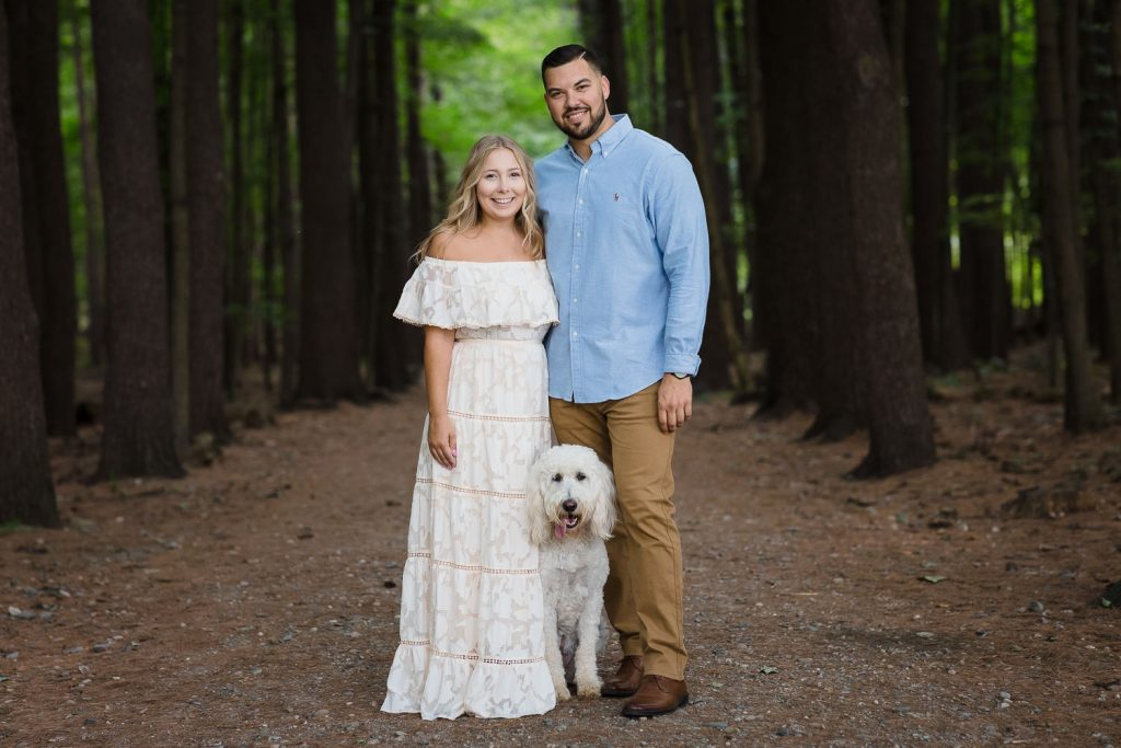 Couple posing along a hiking trail in Saratoga Spa State Park in Saratoga Springs, NY for their engagement photos with their dog