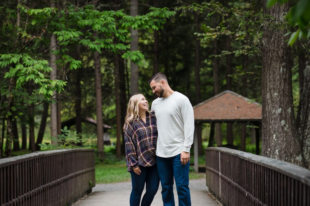 A couple posing for fall engagement photos near the creek in Saratoga Spa State Park in upstate NY