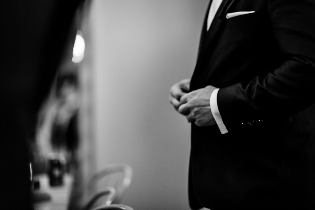 Groom buttons his suit jacket