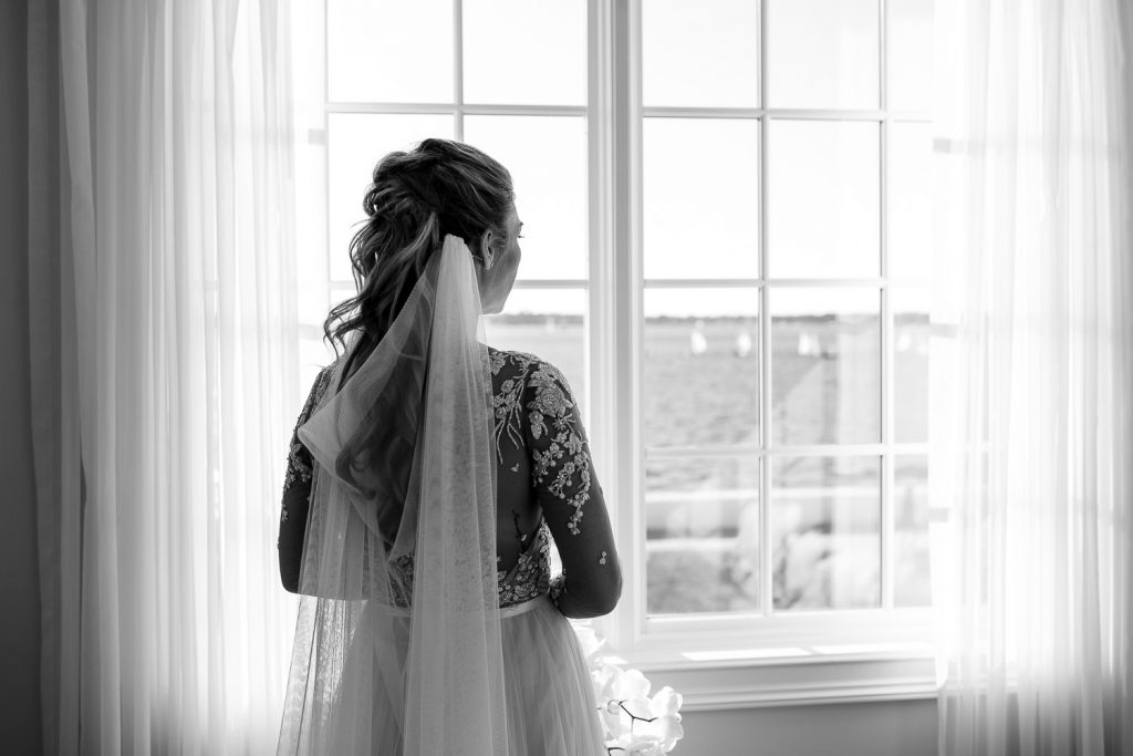 bride looks out window to belle mer ceremony site