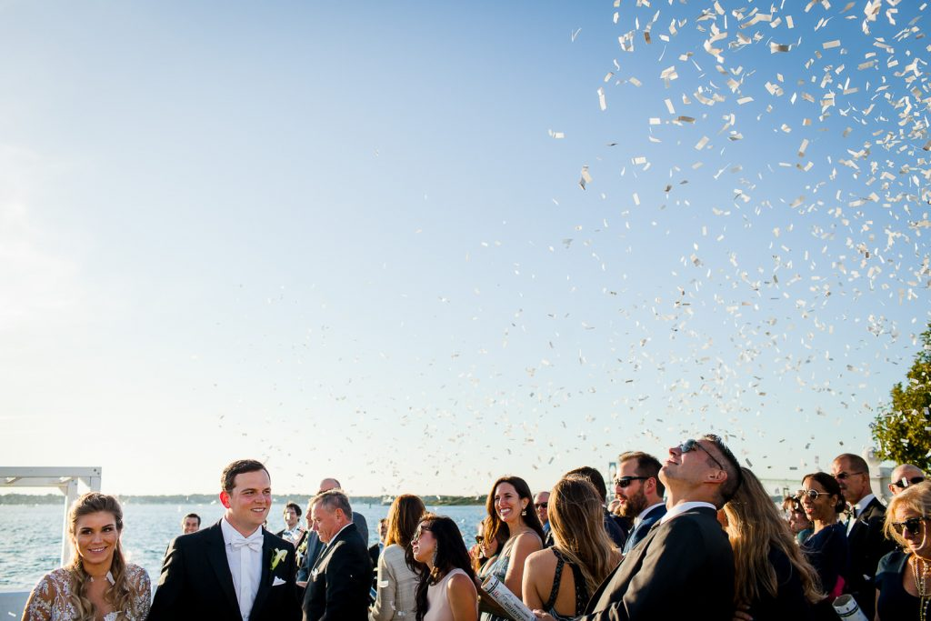 bride and groom exit ceremony amidst confetti