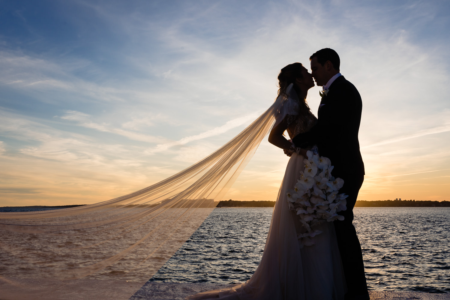 bride with veil and groom silhouetted against a sunset sky