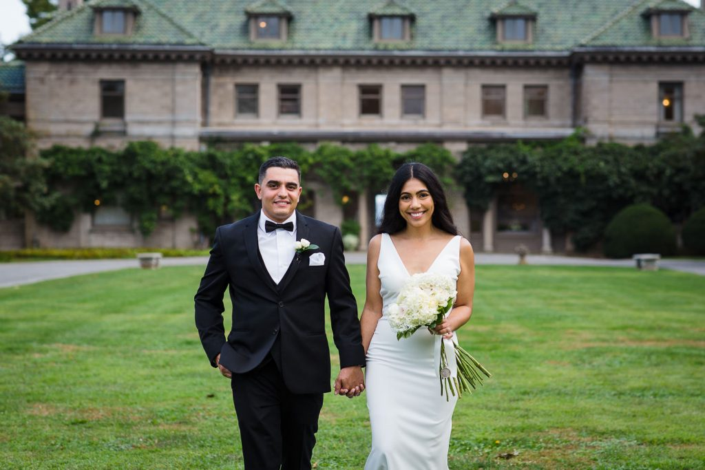 Wedding couple pose for formal photos in front of Eolia Mansion at Harkness Memorial Park in waterford ct
