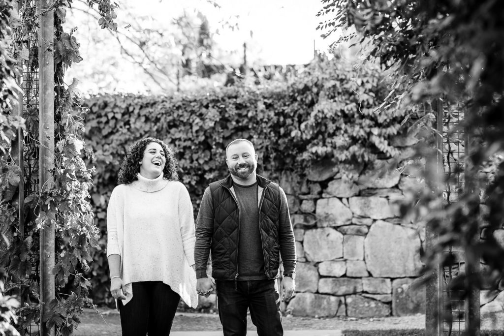 engaged couple walk and laugh