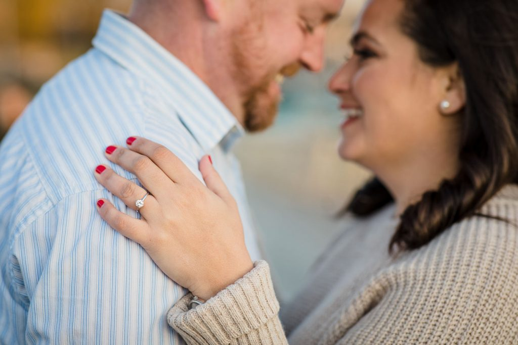 engagement ring with couple laughing