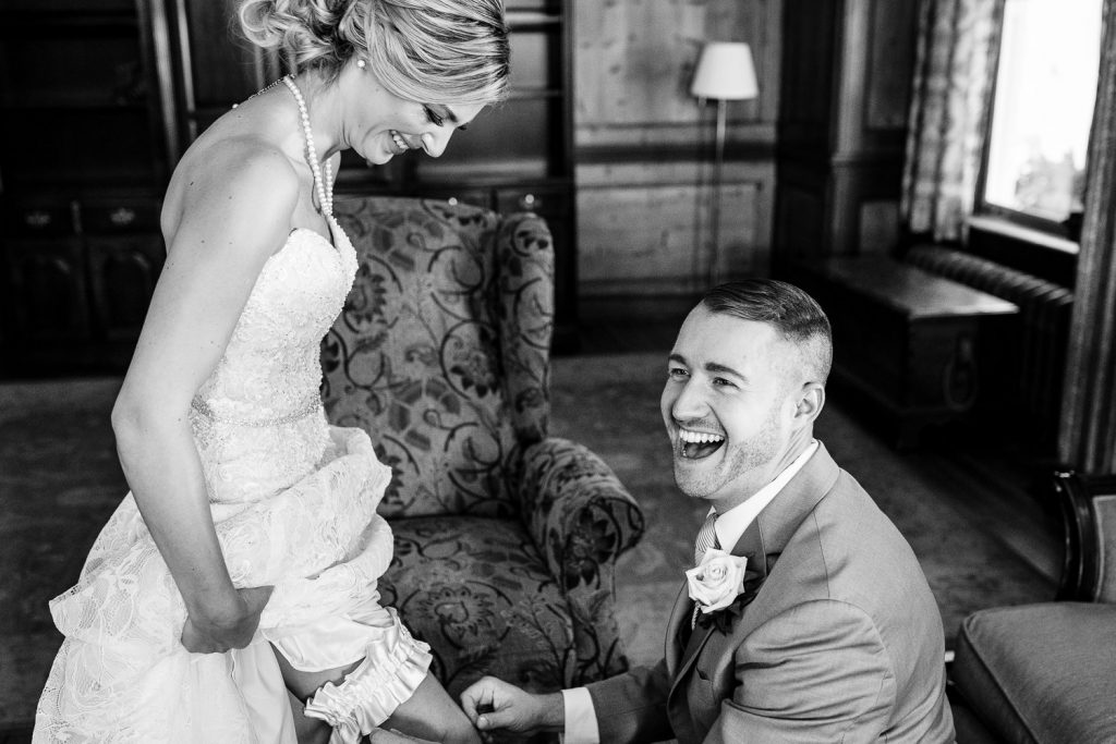 Bridesman laughs as he puts on brides garter