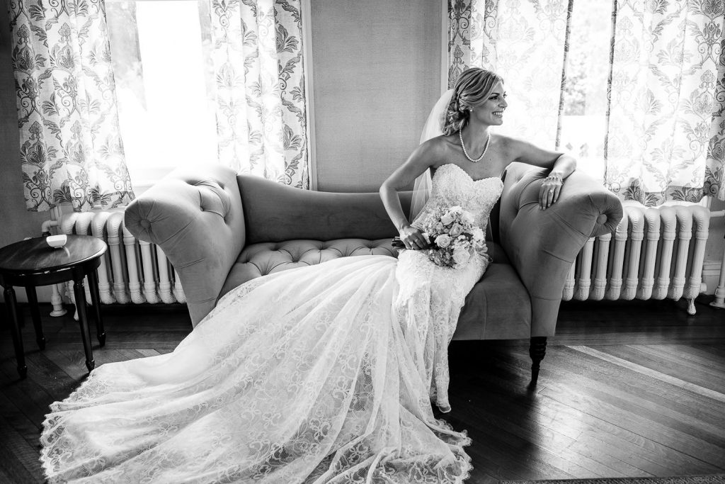 Bride poses for a portrait on a chaise lounge