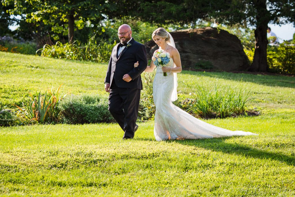 Brides dad walking her down the grassy aisle