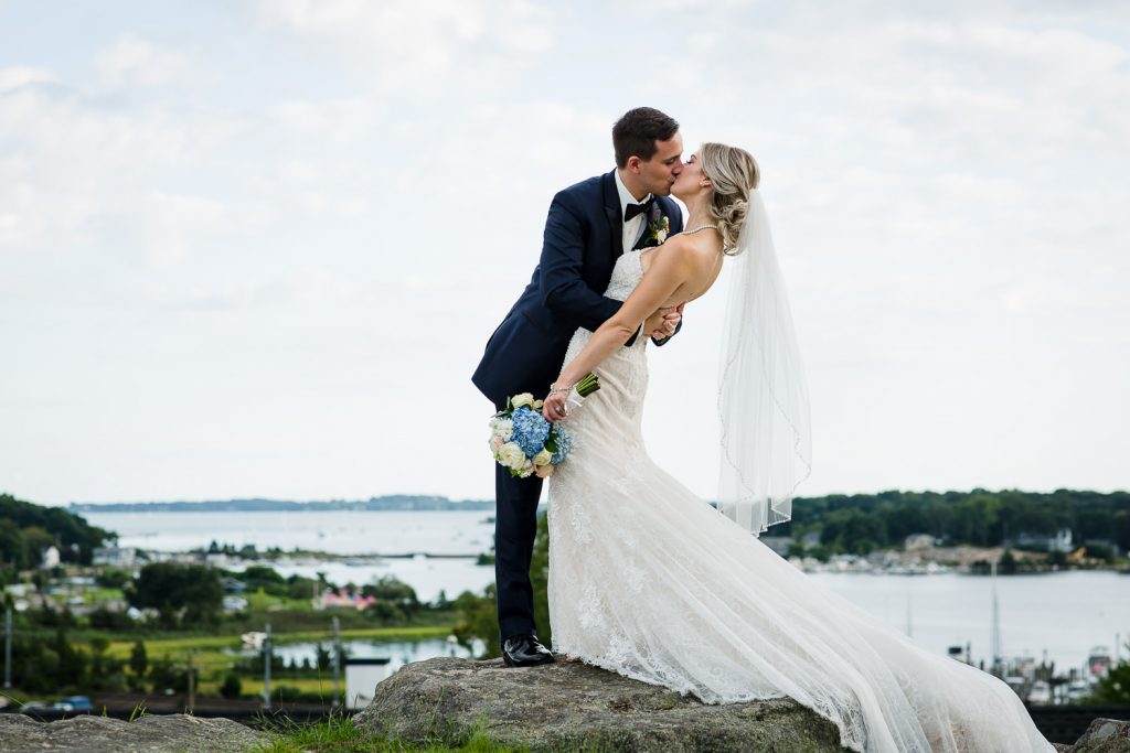 Bride and groom kiss with views of mystic ct
