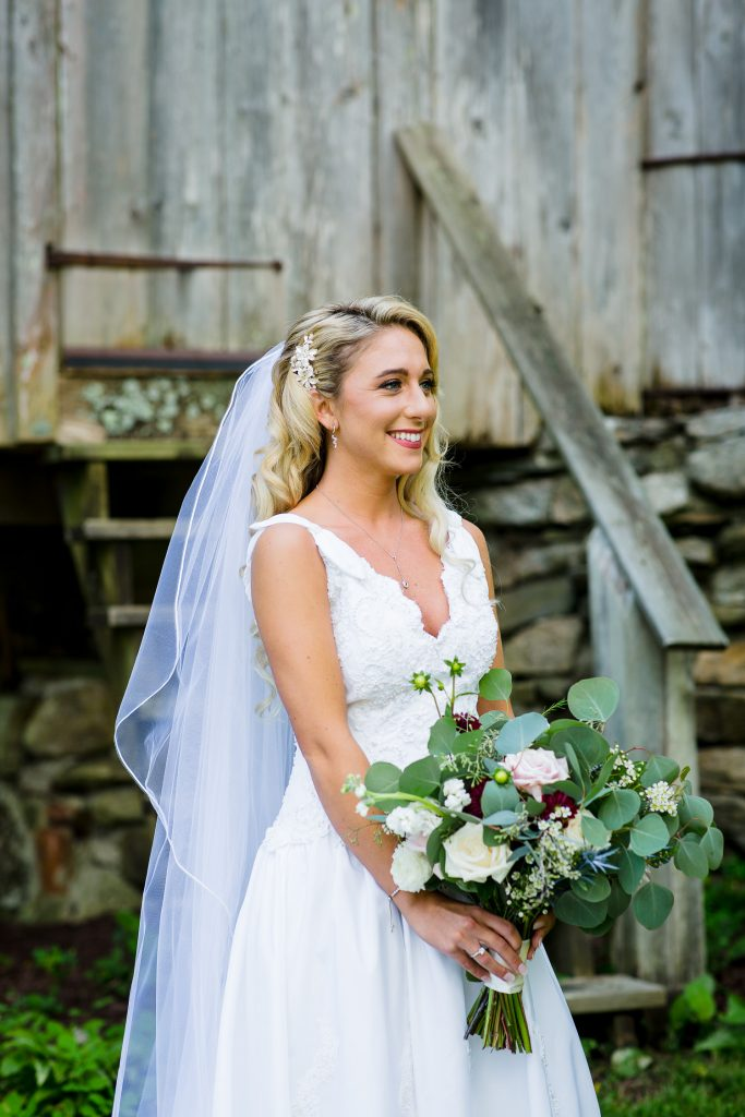 Bride smiles in front of wooden silo