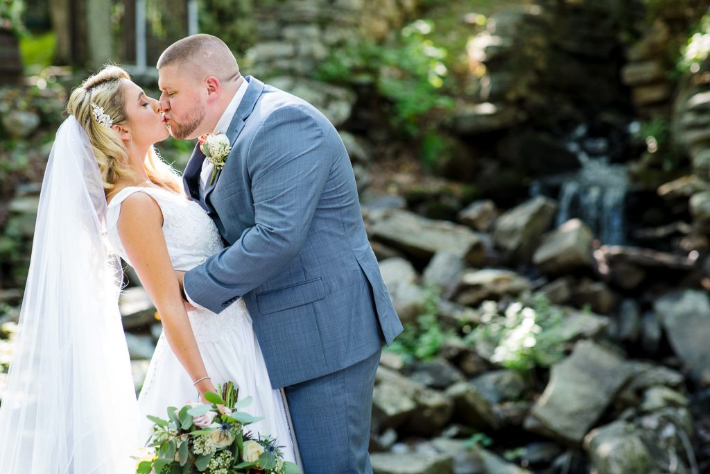 Bride and groom kiss at Wrights Mill Farm waterfall
