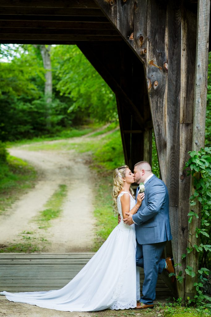 Bride and groom on covered bridge at wrights mill farm
