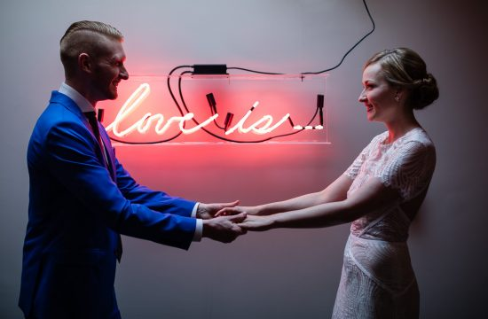 bride and groom first look in front of neon love is sign