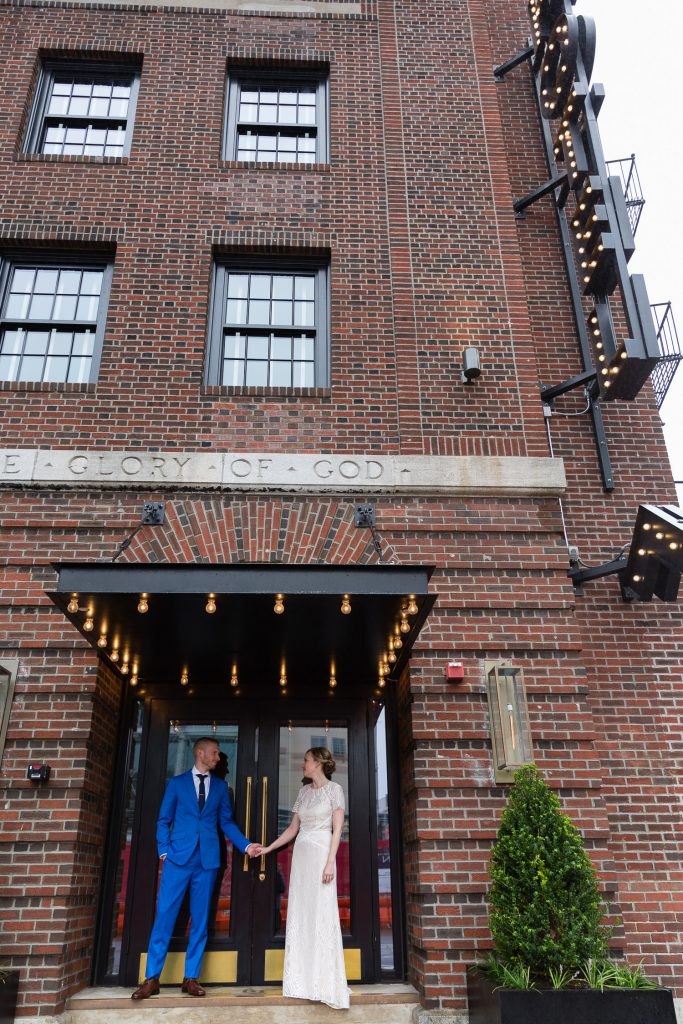 bride and groom under neon sign at dean hotel
